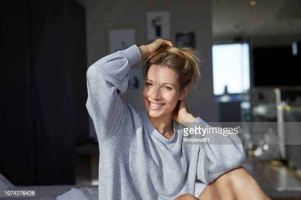 portrait of smiling woman sitting on bed in the morning - sweatshirt stock pictures, royalty-free photos & images
