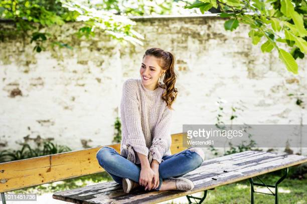 portrait of smiling woman sitting on beer table at courtyard - 胡坐 ストックフォトと画像