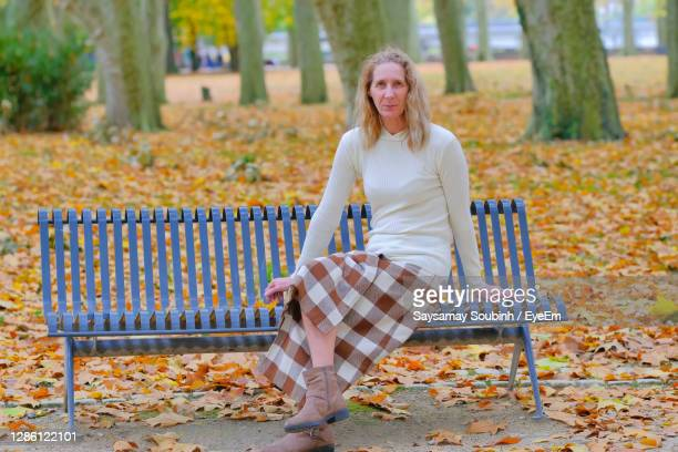 portrait of smiling woman sitting on bench at park - ブザンソン ストックフォトと画像