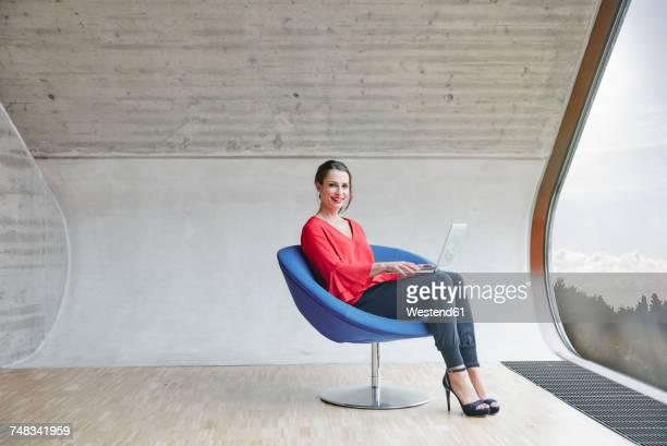 Portrait of smiling woman sitting on chair in attic office with laptop
