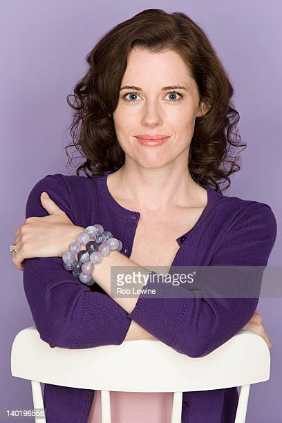 Portrait of smiling woman sitting on chair with purple background, studio shot