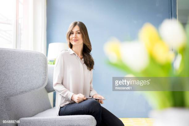 portrait of smiling woman sitting on couch holding tablet - blouse stock pictures, royalty-free photos & images