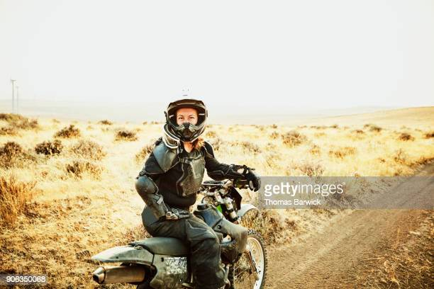 Portrait of smiling woman sitting on dirt bike during desert ride on summer evening