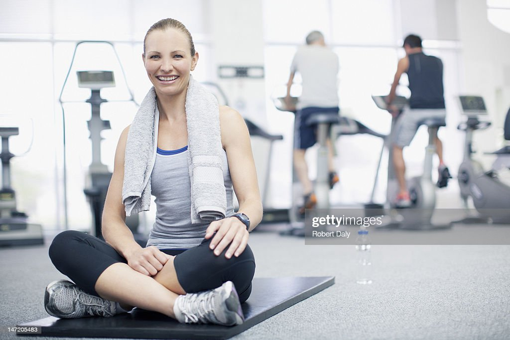 Portrait of smiling woman sitting on exercise mat in gymnasium : Stock Photo