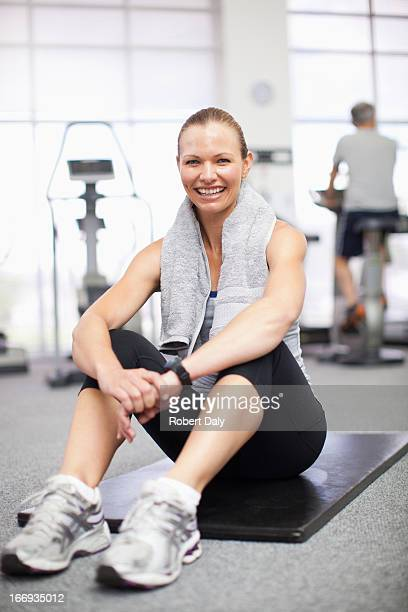 Portrait of smiling woman sitting on exercise mat in gymnasium