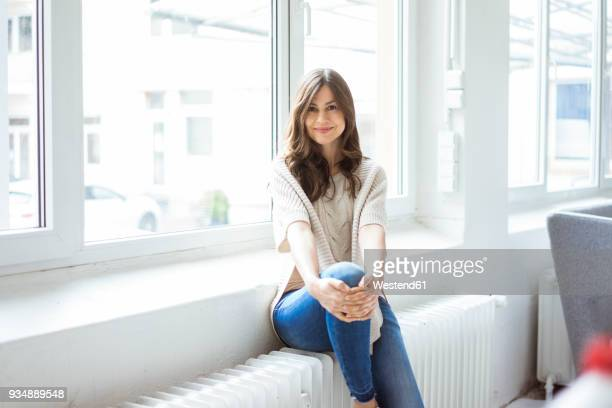 portrait of smiling woman sitting on heater in bright room with window - calientes fotografías e imágenes de stock