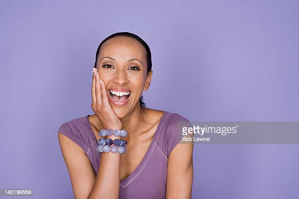 Portrait of smiling woman sitting on purple background, studio shot