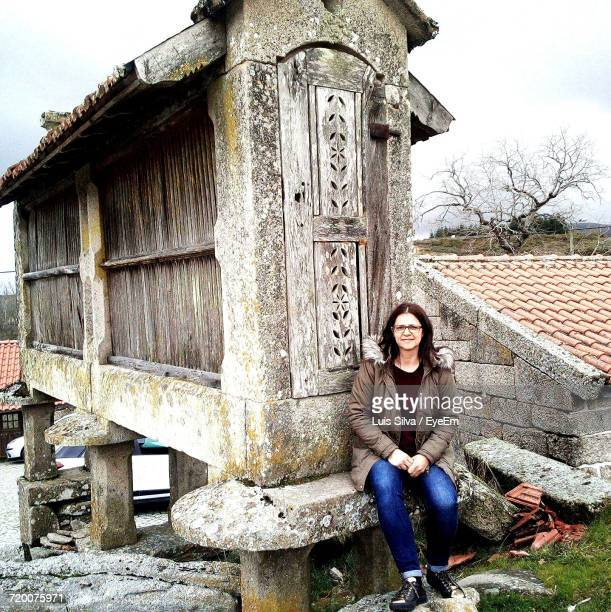 Portrait Of Smiling Woman Sitting On Retaining Wall Against Old Historic Building
