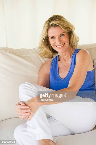 portrait of smiling woman sitting on sofa - sleeveless stock pictures, royalty-free photos & images