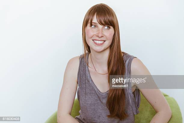 Portrait of smiling woman sitting on soft chair in front of white background