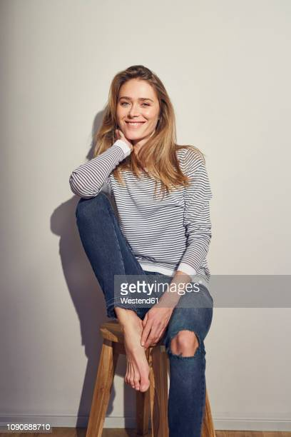 portrait of smiling woman sitting on stool - donne bionde scalze foto e immagini stock