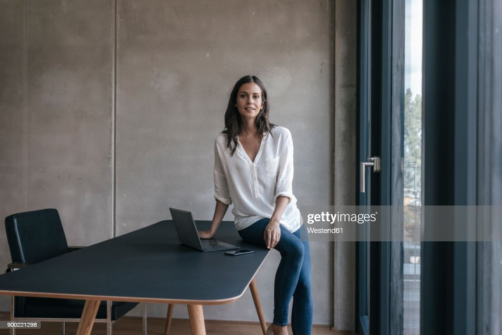 Portrait of smiling woman sitting on table with laptop and cell phone : Stock-Foto