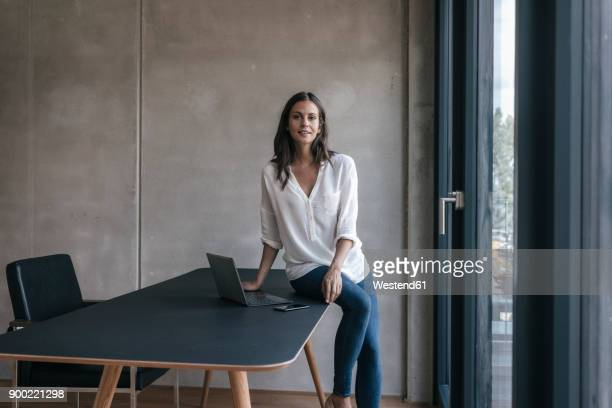 portrait of smiling woman sitting on table with laptop and cell phone - unabhängigkeit stock-fotos und bilder