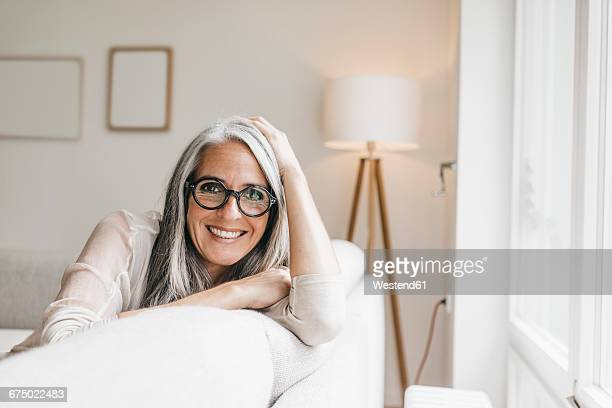 Portrait of smiling woman sitting on the couch at home