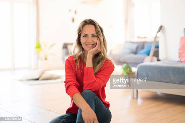 portrait of smiling woman sitting on the floor at home - kin in de hand stockfoto's en -beelden