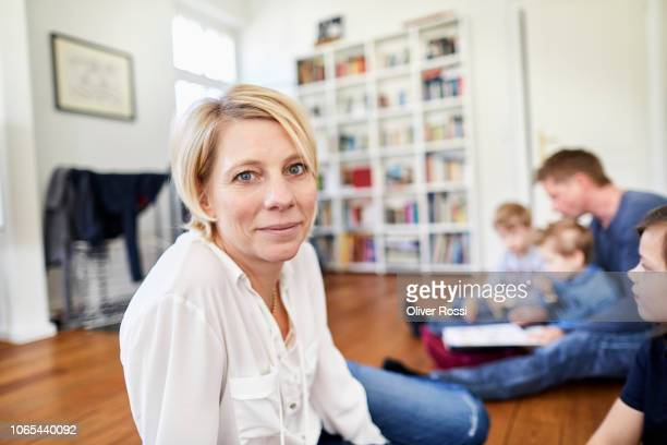 portrait of smiling woman sitting on the floor with family in background - 40 49 jaar stockfoto's en -beelden