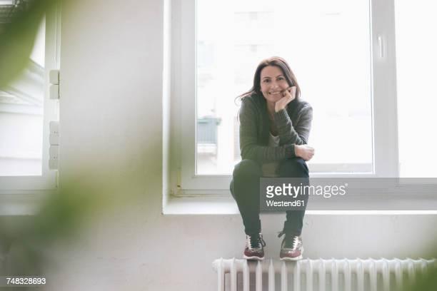 Portrait of smiling woman sitting on window sill in a loft