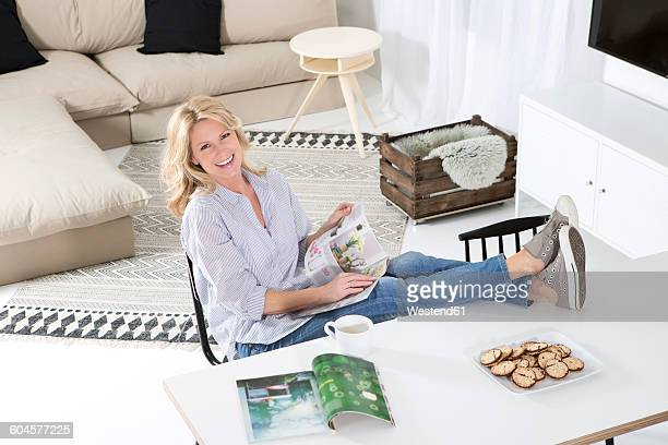 Portrait of smiling woman sitting with feet up on the table in her living room