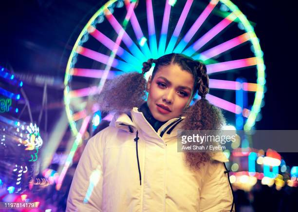 portrait of smiling woman standing against illuminated ferris wheel at night - focus on foreground stock pictures, royalty-free photos & images