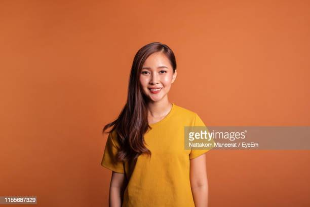 portrait of smiling woman standing against orange background - orange farbe stock-fotos und bilder