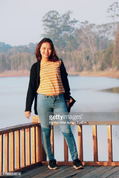 portrait of smiling woman standing against railing - ko ko htike aung stock pictures, royalty-free photos & images