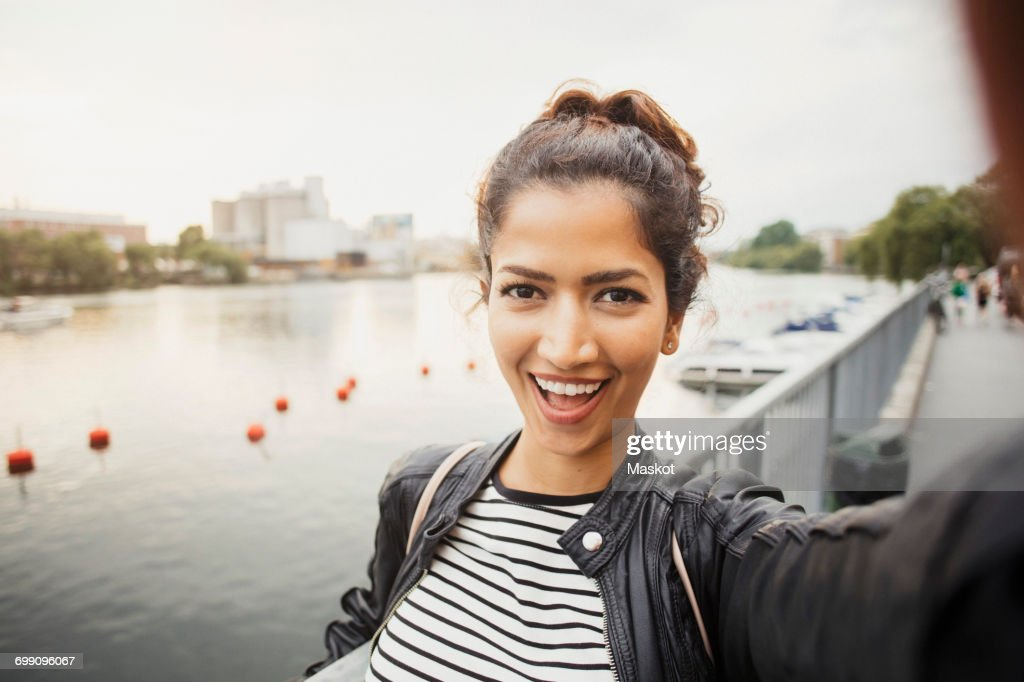 Portrait of smiling woman standing against river in city : Stock Photo