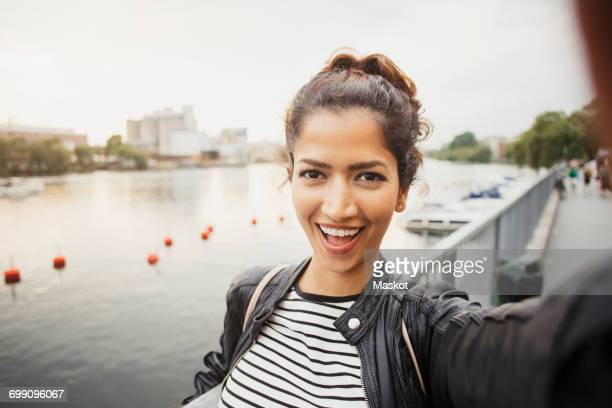 Portrait of smiling woman standing against river in city