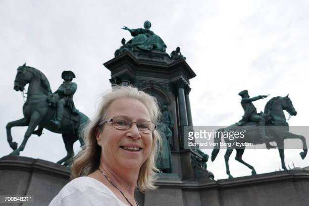 Portrait Of Smiling Woman Standing Against Statues At Hofburg Palace