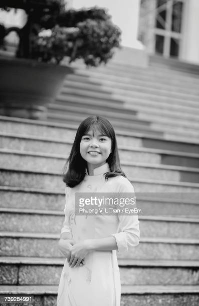 Portrait Of Smiling Woman Standing Against Steps