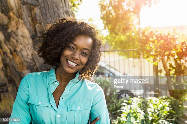 Portrait of smiling woman standing against tree