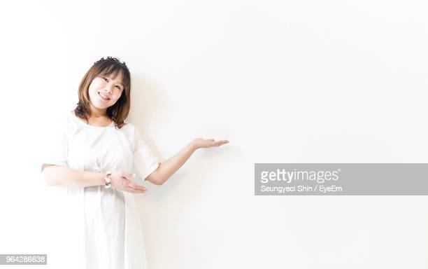 Portrait Of Smiling Woman Standing Against White Background