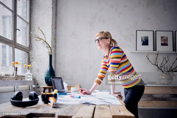 portrait of smiling woman standing at desk in a loft looking through window - pequeña empresa fotografías e imágenes de stock