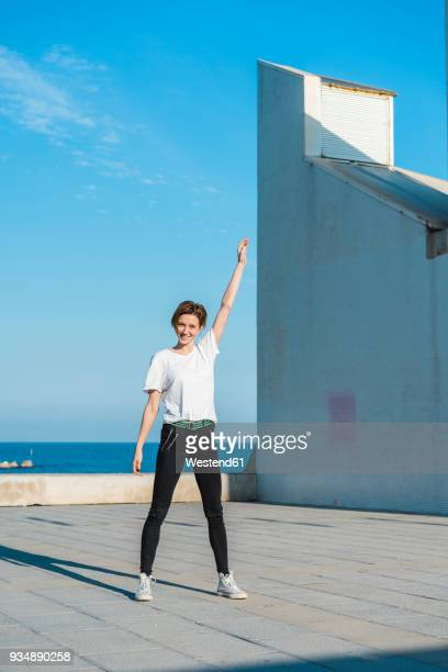 portrait of smiling woman standing at sunlight - arms raised stock pictures, royalty-free photos & images