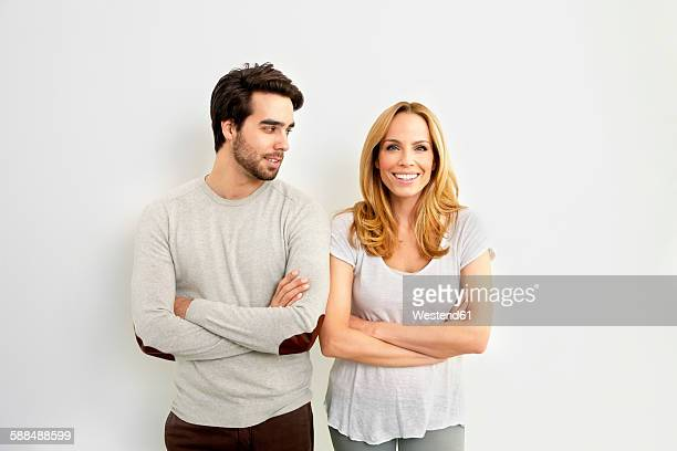 portrait of smiling woman standing besides young man watching her in front of white background - side by side stock photos and pictures