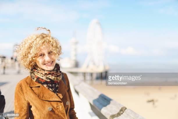 portrait of smiling woman standing by beach - bortes stockfoto's en -beelden