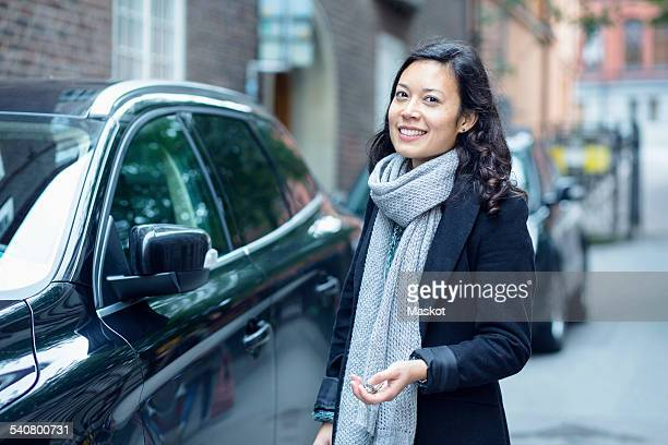Portrait of smiling woman standing by car on street