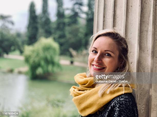 portrait of smiling woman standing by column - carnet stock photos and pictures