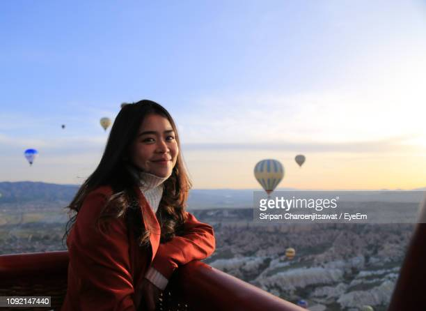 portrait of smiling woman standing by railing against sky during sunset - hot air balloon stock pictures, royalty-free photos & images