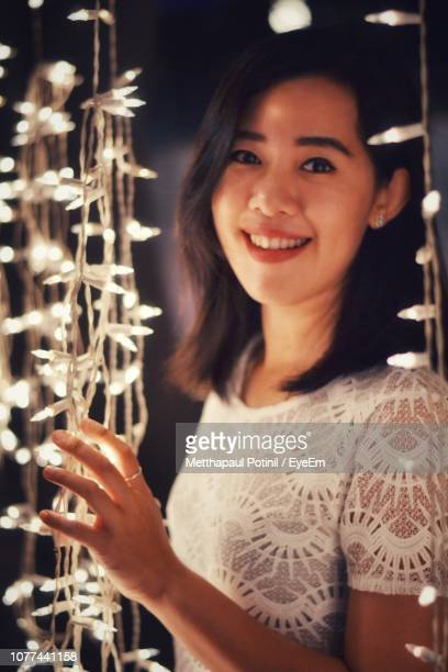 portrait of smiling woman standing by string light - metthapaul stock photos and pictures