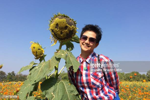 Portrait Of Smiling Woman Standing By Sunflowers On Farm Against Blue Sky