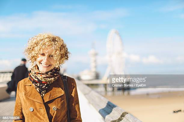 portrait of smiling woman standing by the beach - bortes stock-fotos und bilder