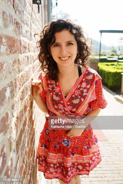 portrait of smiling woman standing by wall - one young woman only stock pictures, royalty-free photos & images