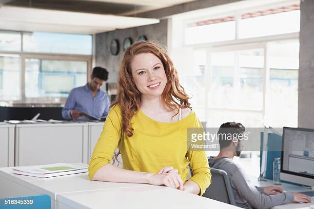 Portrait of smiling woman standing in an open space office