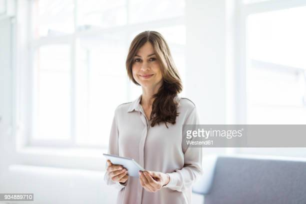 portrait of smiling woman standing in bright room holding tablet - bluse stock-fotos und bilder