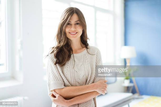 portrait of smiling woman standing in bright room with window - 40 44 jaar stockfoto's en -beelden