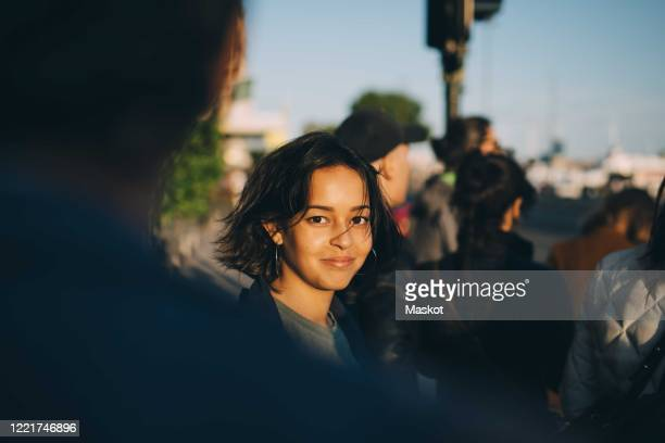 portrait of smiling woman standing in city - incidental people stock pictures, royalty-free photos & images