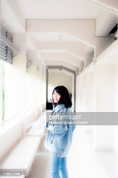 portrait of smiling woman standing in corridor - pattanasit stock pictures, royalty-free photos & images
