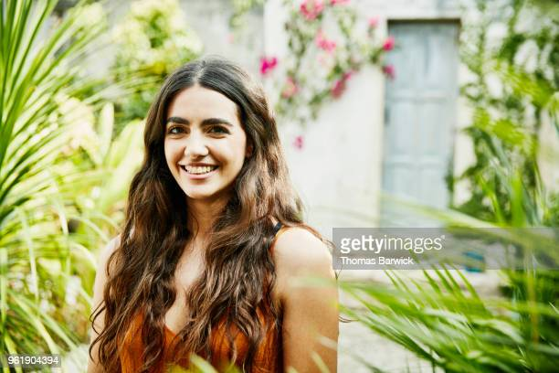 Portrait of smiling woman standing in courtyard of outdoor spa