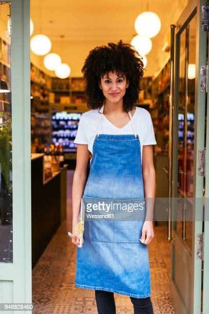 Portrait of smiling woman standing in entrance door of a store