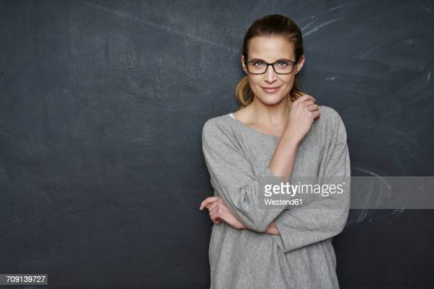 portrait of smiling woman standing in front of blackboard - 35 39 jahre stock-fotos und bilder